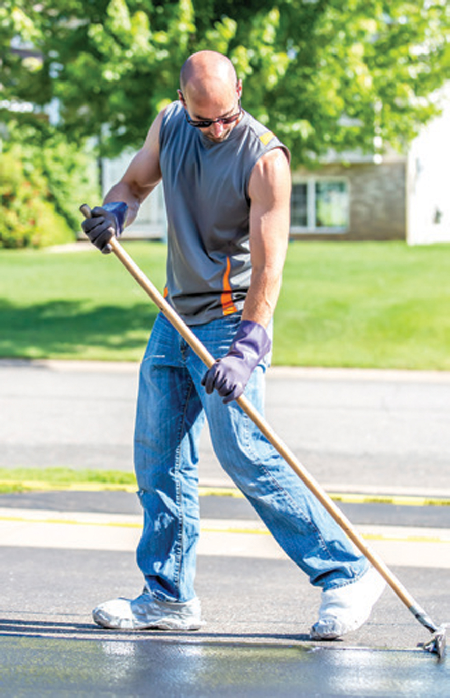 Man Seal Coating His Driveway On A Summer Day